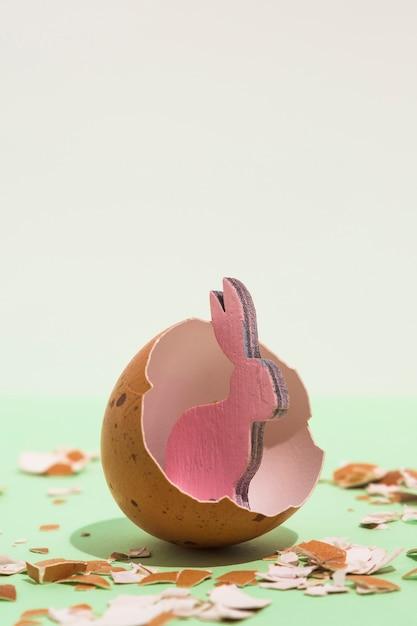 Kleines rosa hölzernes kaninchen im defekten ei Kostenlose Fotos
