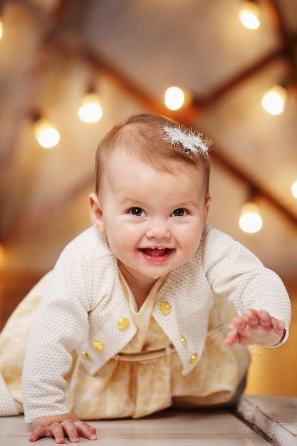 Kleines schönes mädchen in einem kleidspaß kriecht Premium Fotos