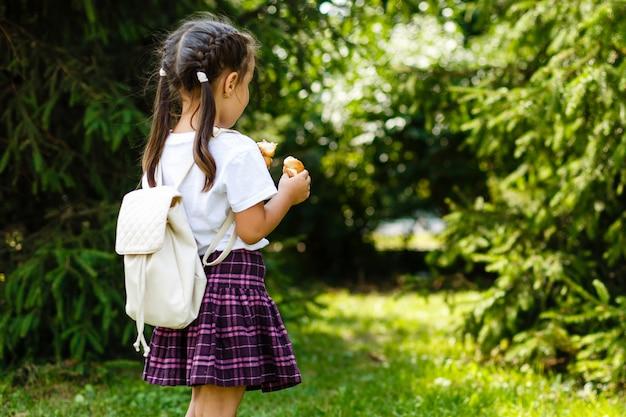 Kleines schulmädchen, das hörnchen im park isst. zurück in die schule im freien Premium Fotos