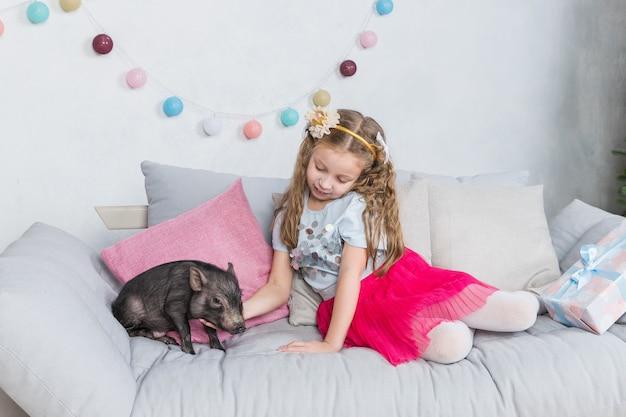 Kleines schwarzes schwein und kleines mädchen Premium Fotos