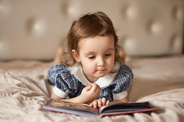 Kleines süßes mädchen in einem retro-kleid, das ein buch liest. Premium Fotos