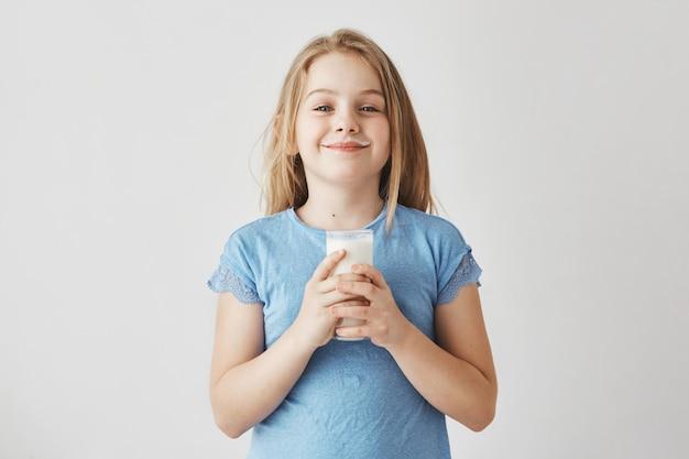 Kleines süßes mädchen mit blonden haaren im blauen t-shirt mit milchtropfen auf gesicht, glücklich, ihren tag mit großem glas des gesunden getränks zu beginnen. Kostenlose Fotos