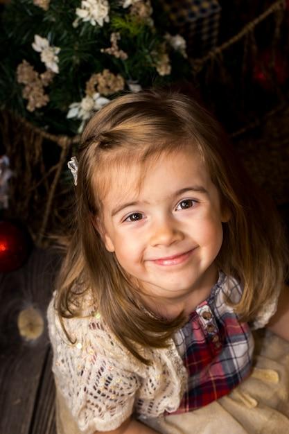 Kleines süßes mädchen mit einem spielzeug santa in den händen sitzt auf einem holzboden mit weihnachtsdekor Kostenlose Fotos