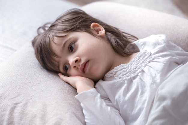 Kleines süßes mädchen traurig im bett, schlafkonzept Kostenlose Fotos