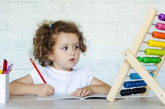 Kleines vorschulkind, das mathematik lernt. kind zählt auf die konten. entwicklung, erziehung, unterricht und ausbildung von kindern. Premium Fotos