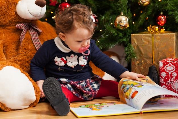 Kleinkind-babylesemärchen nähern sich weihnachtsbaum. Premium Fotos