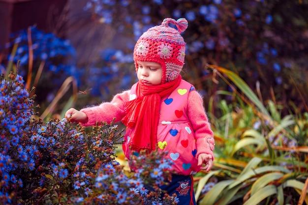 Kleinkind, das in den blumen steht Premium Fotos