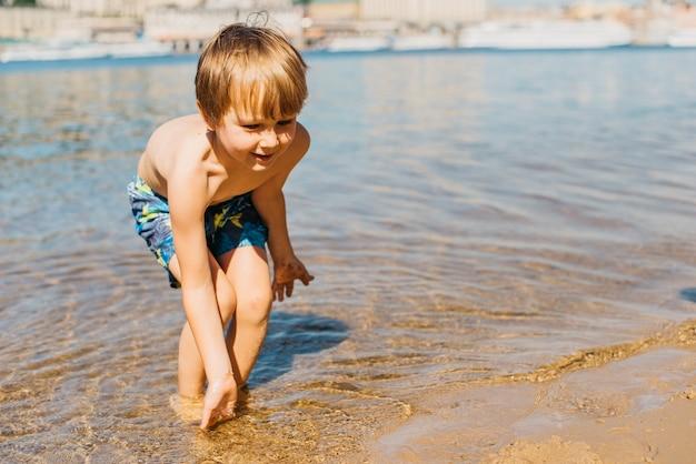 Kleinkind, das in meer spielt Kostenlose Fotos