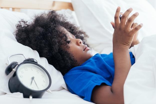 Kleinkind, das smartphone mit dem wecker zu viel zeit zu zählen morgens verwendet Premium Fotos