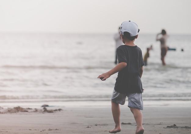 Kleinkind, das zu einem sandstrand läuft Premium Fotos