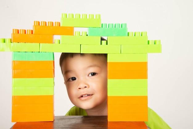 Kleinkind des kleinen jungen, das den plastikziegelsteinblock bunt mit glücklichem spielt Premium Fotos