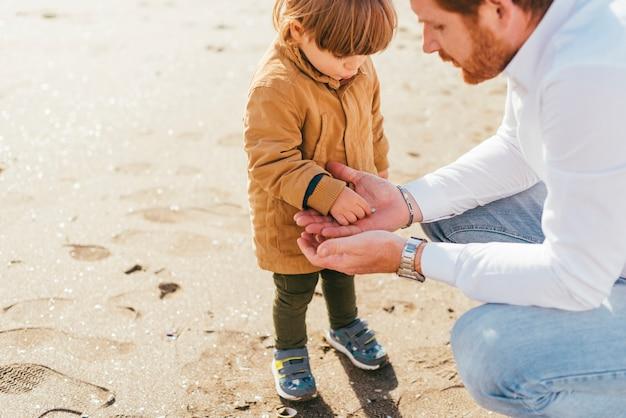 Kleinkind im mantel, der mit vati spielt Kostenlose Fotos
