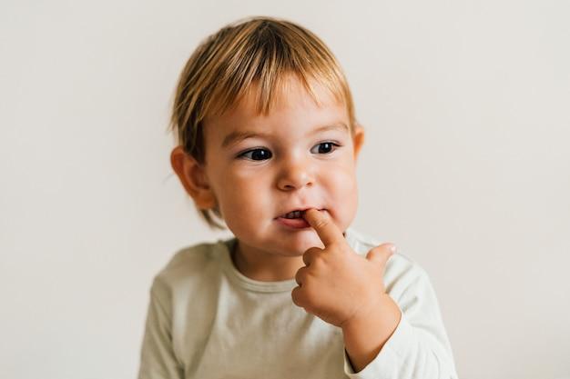 Kleinkind mit dem finger im mund. kinderkrankheiten schnarchen zahnfleisch konzept Premium Fotos