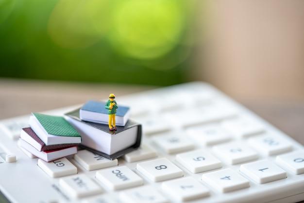 Kleinkinder miniaturleute, die auf büchern und weißem taschenrechner stehen Premium Fotos