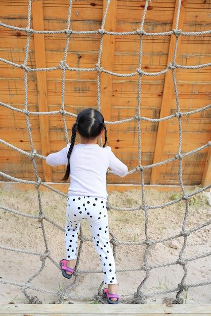 Kleinkindmädchen der hinteren ansicht am spielplatz, der auf kletterndem seilnetz spielt. Premium Fotos