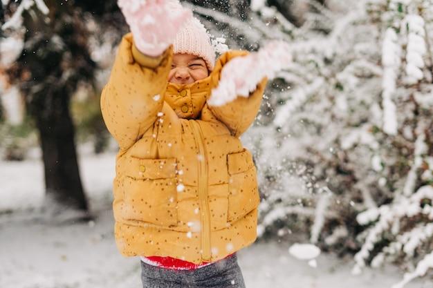 Kleinkindmädchen glücklich mit schneetag im winter. in den weihnachtsferien draußen spielen Premium Fotos