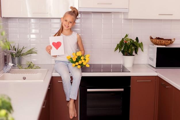 Kleinkindmädchen mit einem blumenstrauß und einer postkarte, die in der küche sitzen. Premium Fotos