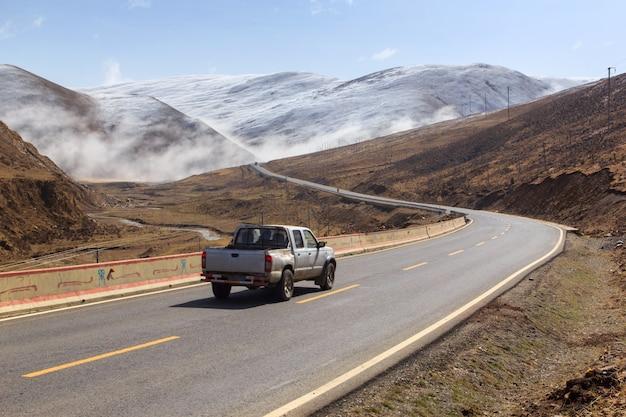 Kleintransporter auf der straße, schöne winterstraße in tibet unter schneeberg sichuan china Premium Fotos