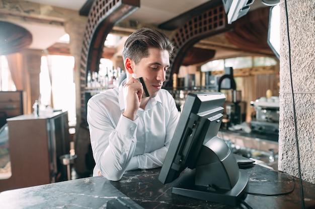 Kleinunternehmen, leute und service - glücklicher mann oder kellner im schutzblech am zähler mit der geldkassette, die an der bar oder an der kaffeestube arbeitet. Premium Fotos