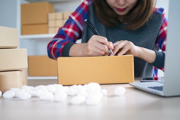 Kleinunternehmer schreiben namen, um die auslieferung von paketen an kunden vorzubereiten. kleinunternehmen, die online verkaufen und produkte online bestellen Premium Fotos
