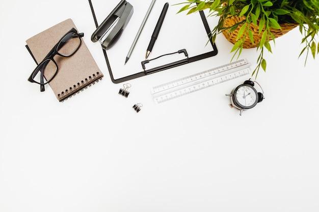 Klemmbrett mit büroartikel auf weißer tabelle Premium Fotos