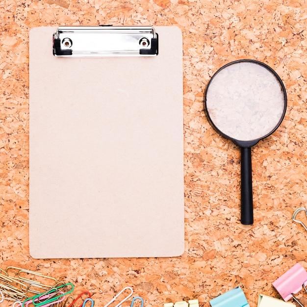 Klemmbrett mit vergrößerungsglas und mehrfarbigen büroklammern auf korkenhintergrund Kostenlose Fotos