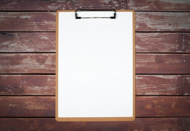 Klemmbrett mit weißem blatt auf braunem hölzernem hintergrund Premium Fotos