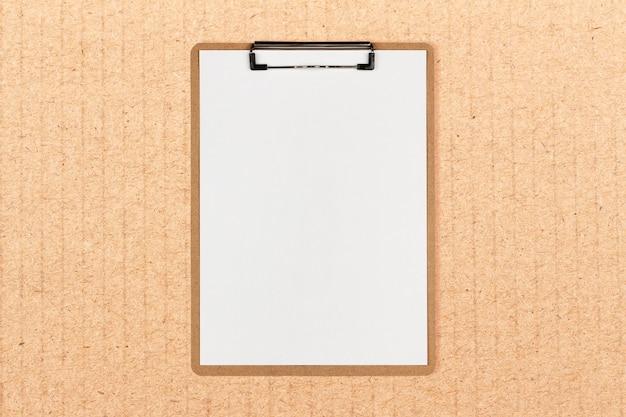 Klemmbrett mit weißem blatt und platz für text auf kraftpapierhintergrund Premium Fotos