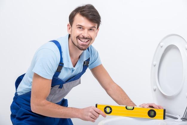 Klempner mit der gebäudeebene während der arbeit. Premium Fotos
