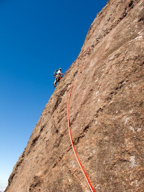Kletterer, der eine abfallende felswand in brasilien klettert Premium Fotos