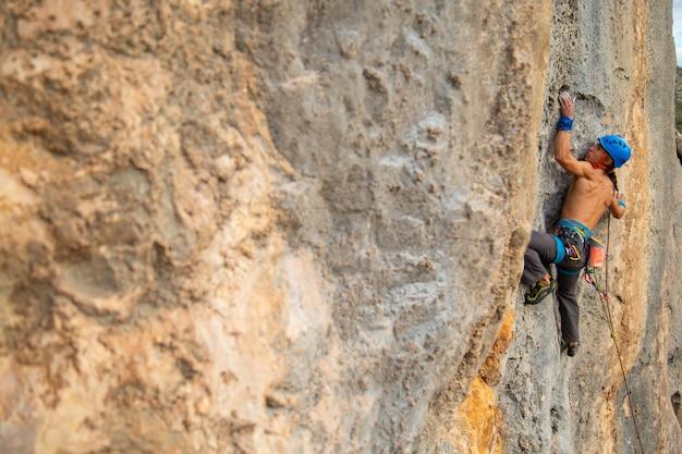 Kletternde bergwand des hemdlosen bergsteigermannes an erstaunlichem sonnigem tag Premium Fotos