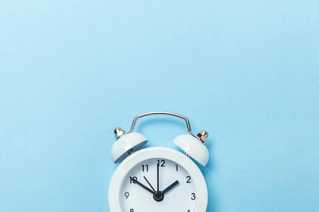 Klingeln des klassischen weckers der doppelglockenweinlese lokalisiert auf blauem pastellhintergrund. Premium Fotos