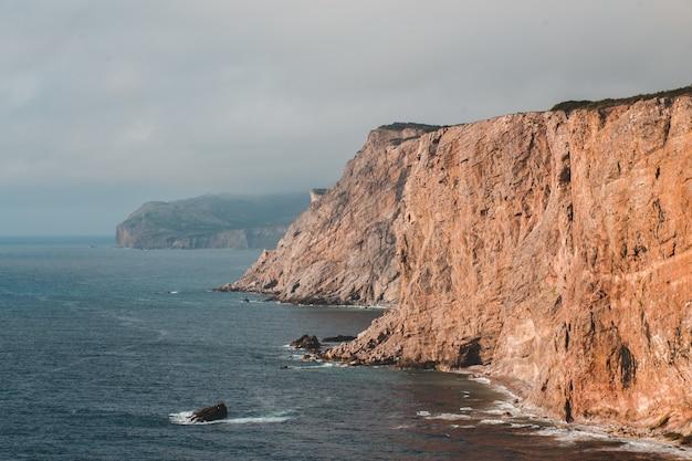 Klippe neben dem ozean Kostenlose Fotos