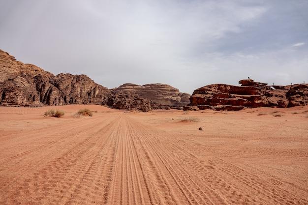 Klippen und höhlen auf einer wüste voller trockenem gras unter einem bewölkten himmel während des tages Kostenlose Fotos