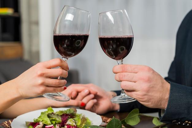 Klirrende gläser der frau wein mit mann bei tisch mit platte Kostenlose Fotos