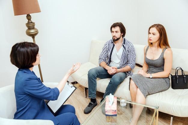 Kluge und gutaussehende leute sitzen vor der psychologin und schauen sie an. doktor spricht mit ihnen und streckt die hand nach ihnen aus. Premium Fotos