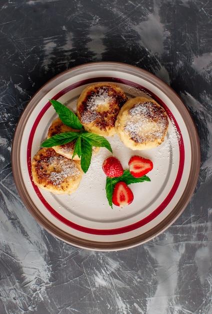 Klumpenpfannkuchen mit erdbeerminze und puderzucker in einer weißen platte. Premium Fotos