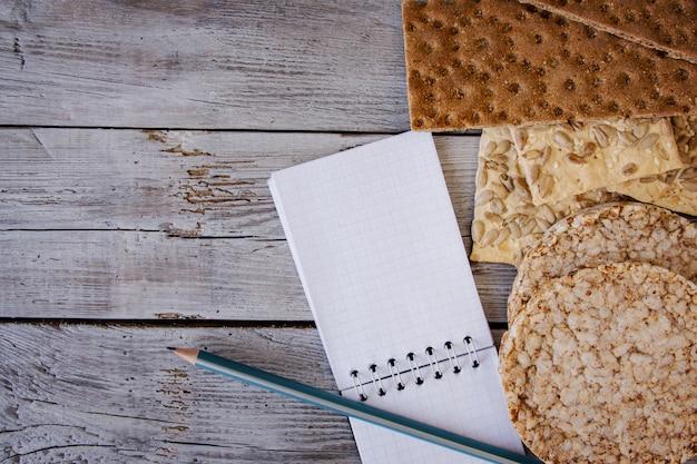 Knäckebrot, flocken, buchweizen, kekse mit sonnenblume auf einem strukturierten hintergrund Premium Fotos