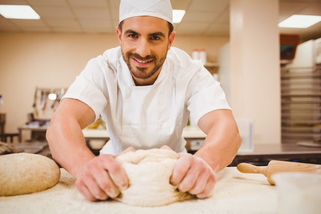 Knetender teig des bäckers an einem zähler in einer handelsküche Premium Fotos