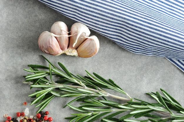 Knoblauch, rosmarin und gewürze mit einer gestreiften tischdecke Premium Fotos