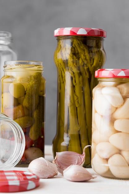 Knoblauch, spargel und oliven in gläsern konserviert Premium Fotos