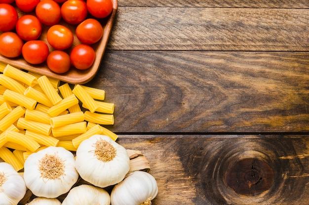 Knoblauch und tomaten in der nähe von pasta Kostenlose Fotos