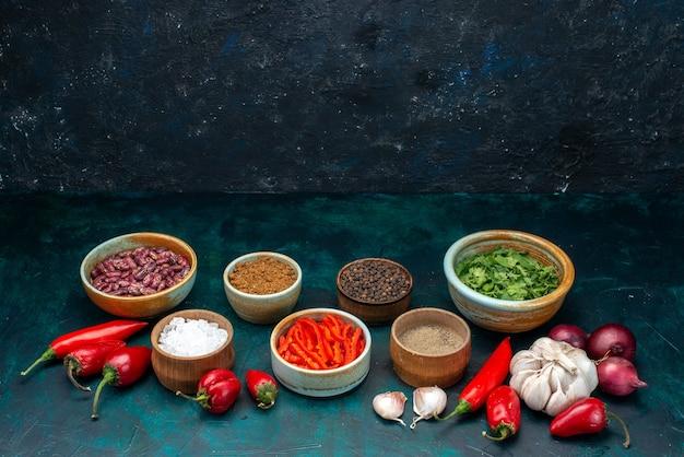 Knoblauch und zwiebeln zusammen mit paprika, gemüse und gewürzen auf dunklem, pflanzlichem pfeffer Kostenlose Fotos