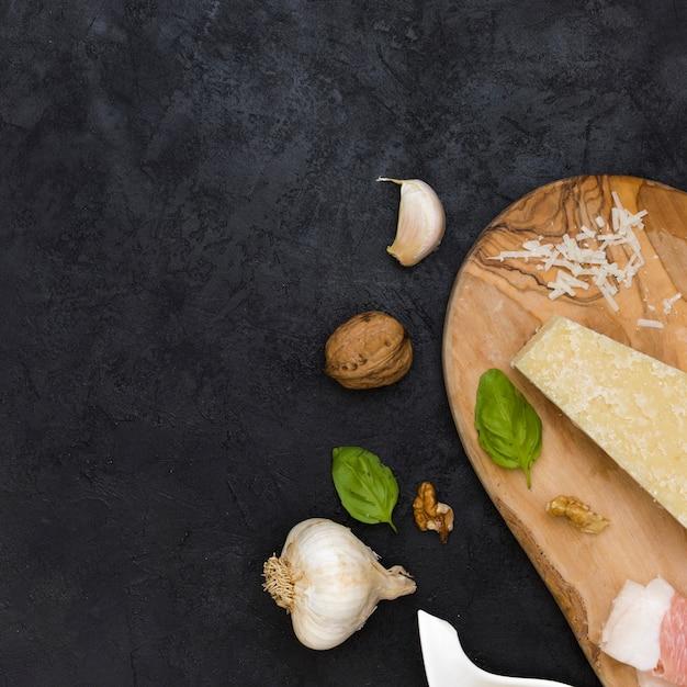 Knoblauchzehe; ganze walnuss; basilikum; käse- und knoblauchclub auf schwarzem strukturiertem hintergrund Kostenlose Fotos