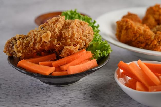 Knusperiges gebratenes huhn auf einer platte mit salat und karotte Kostenlose Fotos