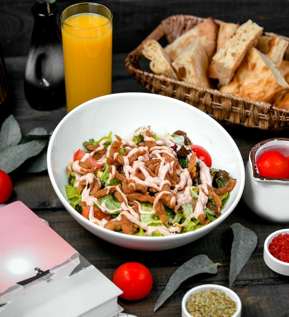 Knusprige hähnchenstreifen mit salat, tomate und mais, garniert mit mayonnaise Kostenlose Fotos