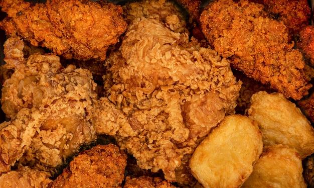 Knuspriges gebratenes huhn und nuggets. fast-food-hintergrund. würzig verspielt Premium Fotos