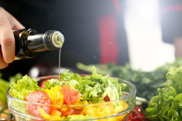 Koch hält flasche in der hand und rieselt olive Premium Fotos