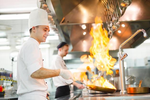 Koch kocht in einem restaurant. Premium Fotos