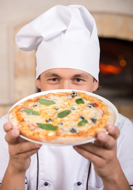 Koch zeigt leckere pizza aus dem ofen. Premium Fotos
